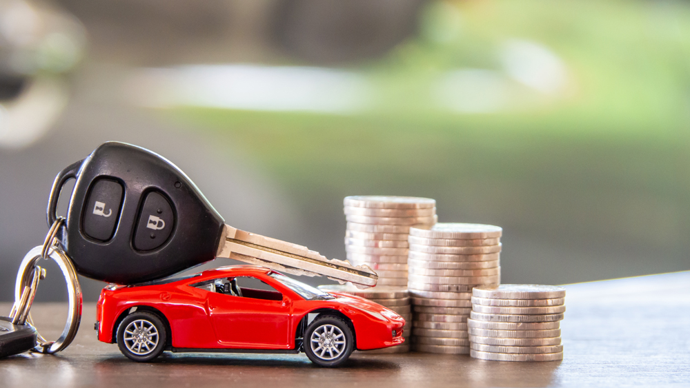 Red,Car,And,Key,On,Stacks,Of,Coin,,Car,Loan